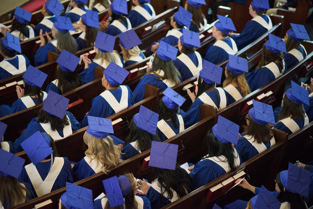 This overhead shot captures rows of seated graduands in blue caps and gowns. The downward angle emphasizes the number of students in the room and offers a visually interesting perspective.