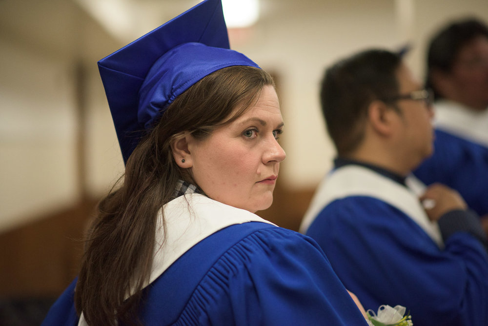 This close-up shot captures a graduate looking over their shoulder with a pensive expression on their face. A shallow depth of field is used to eliminate noise in the background and make the subject the focus of the image.