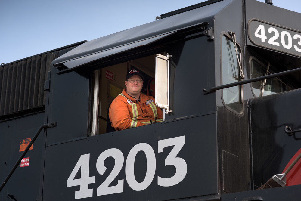 A crew member in an orange jumpsuit sits in the first car of a Cando train. The photograph is taken at a low angle, to include some of the exterior of the train, and provide a sense its height.