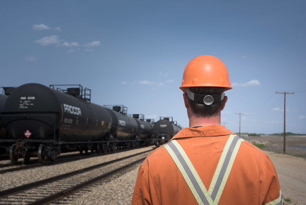 A crew member in an orange jumpsuit and hard hat looks towards the tracks and trains. This photograph captures the employee's view from over his shoulder as he walks along the tracks.