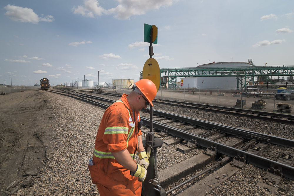 A train approaches in the distance, while an employee works beside the track. This image depicts the vastness of the yard, with an assortment of equipment and facilities visible in the background.
