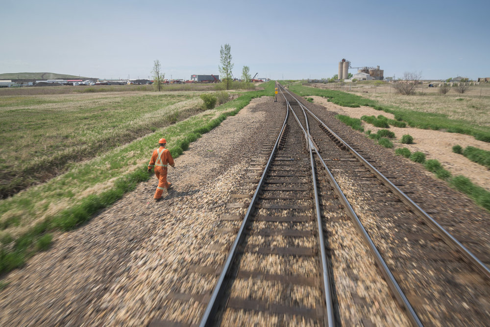 An employee walks on the gravel beside the train tracks towards a section of the track where a switch is located. This photograph is captured in motion, as can be identified by the blurring of the gravel and track in the foreground.