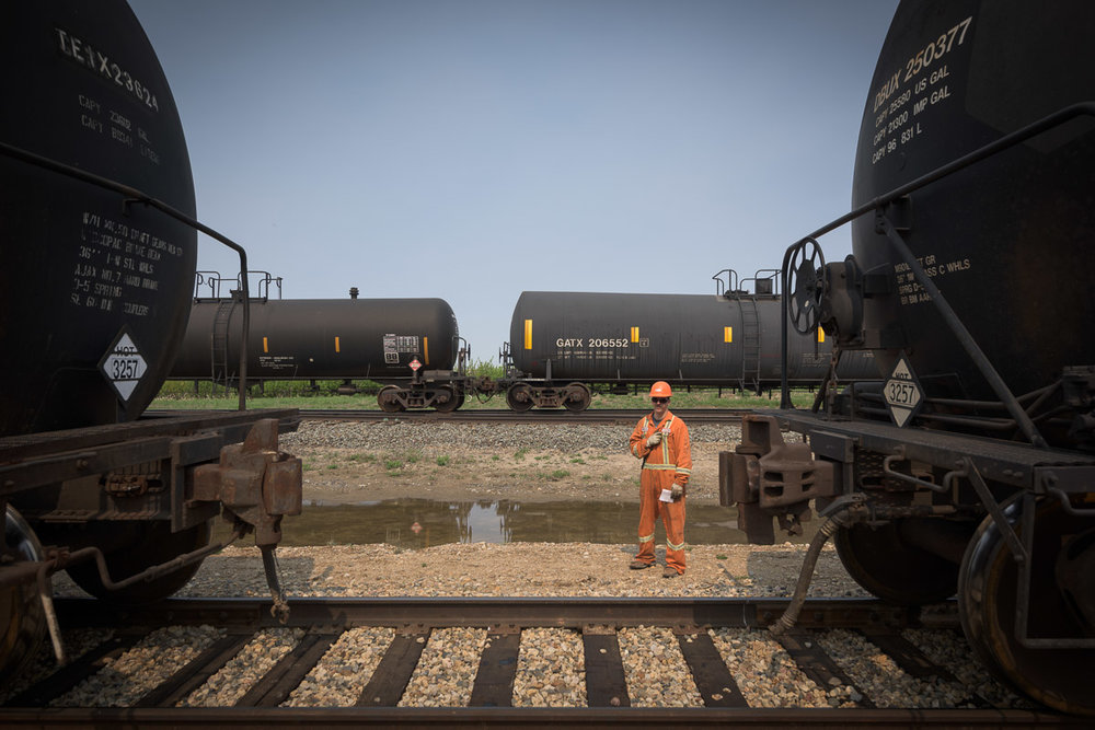 This image accentuates the colossal size of the tank cars by drawing a comparison to the size of an employee who stands beside to cars.