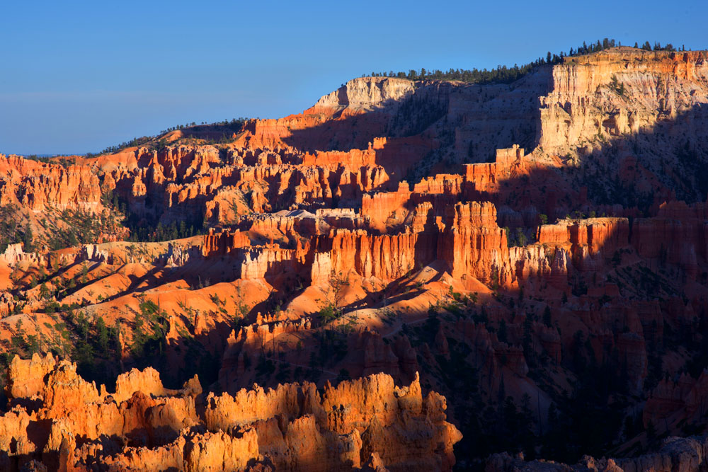 The sun washes across Bryce Canyon causing deep shadows. © Robert Lowdon