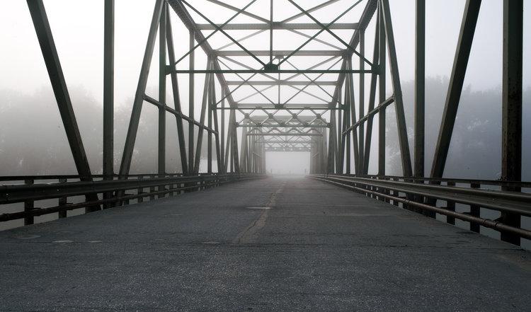 Fog rolls in the early morning on a bridge somewhere near St. Eustache, Manitoba.