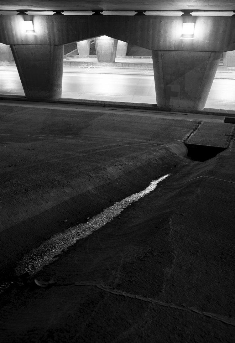 Photograph of a rainy night under the Bishop Grandin bridge.