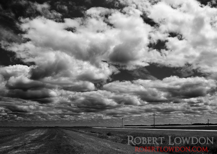 Clouds move across this prairie landscape. © Robert Lowdon  The prairies are best known, for well, how flat they are. The epic skies and fields of endless clouds, seem to be less well known. Here we have a black and white photograph taken in mid day. Can you count how many clouds are in this photo?