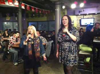 Brandon University President Dr. Deborah Poff, and BUSU President Carissa Taylor take part in karaoke at SUDS during Snowientation. (Jenna Clinton / BUSU)