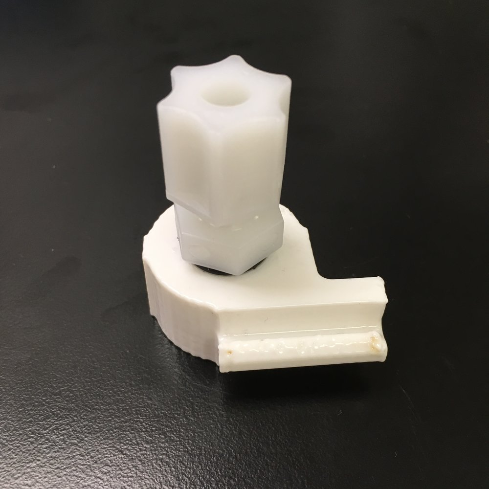 An FDM Printed Bag Cap with an NPT x Compression Fitting attached. It has been post-processed with acetone vapor to smooth the outer surface.