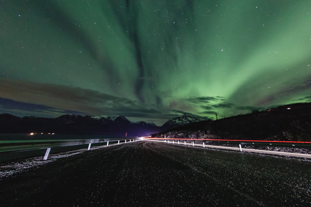 A car's headlights and taillights light up the road as they drive under an incredible green sky.