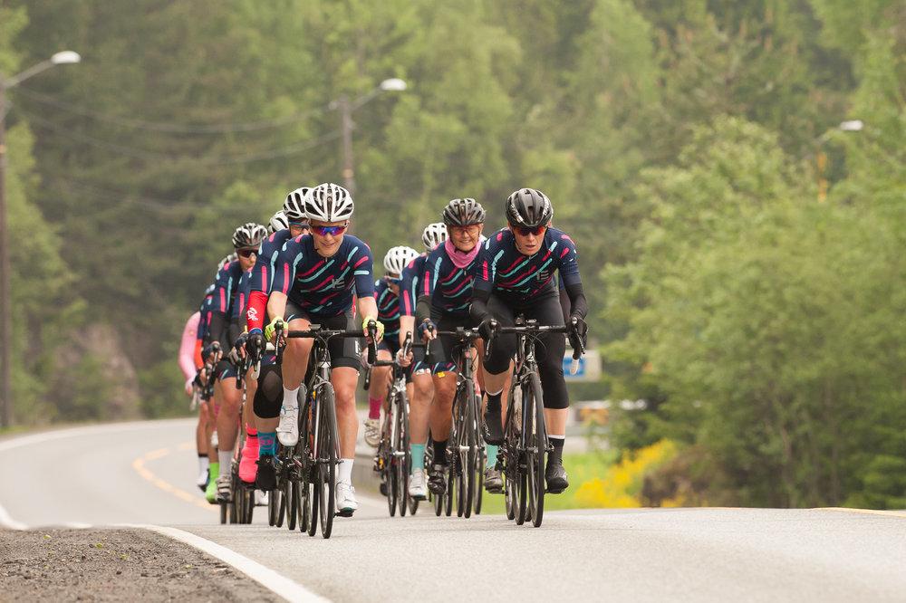 Foto: Helge Langen. Bildet er tatt under Tyrifjorden Rundt 2017 og i front sykler to av tre kapteiner (fra venstre): Heidi R. Sandstø og Malin Johansen. Sissel Vien i bakgrunnen.