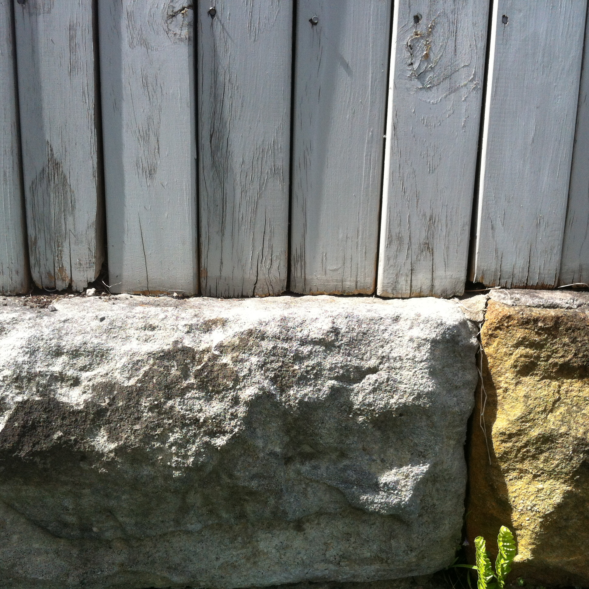 Portion of stone wall and grey painted fence