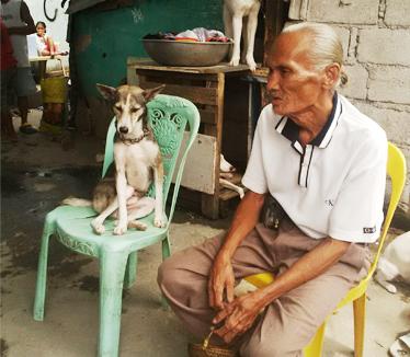 Mang Sergio mit seinem Hund Princess in seinem Haus