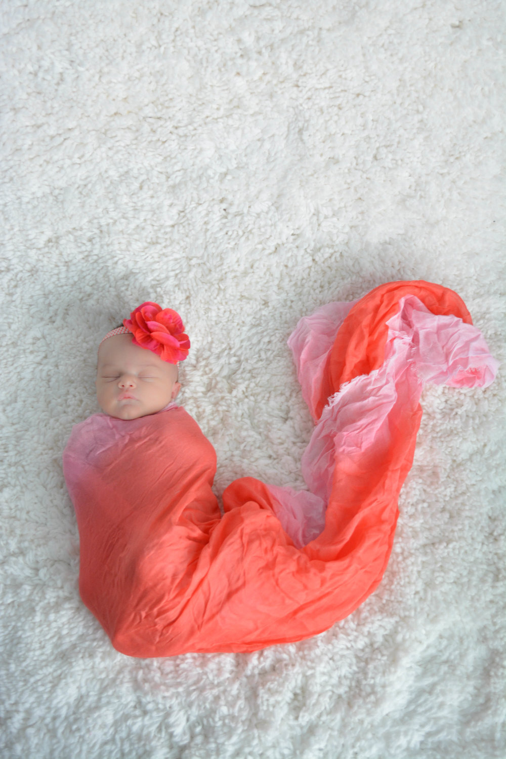 Sleeping newborn girl wrapped in red and pink with a big red and pink flower in her hair