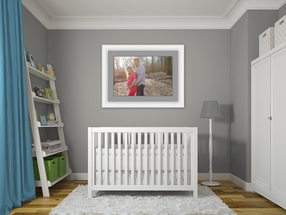 beautiful maternity photo of couple framed and hanging above a crib in a nursery