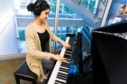 BMus student Serina Mui plays one of the donated pianos.  Photo: UBC Library Communications