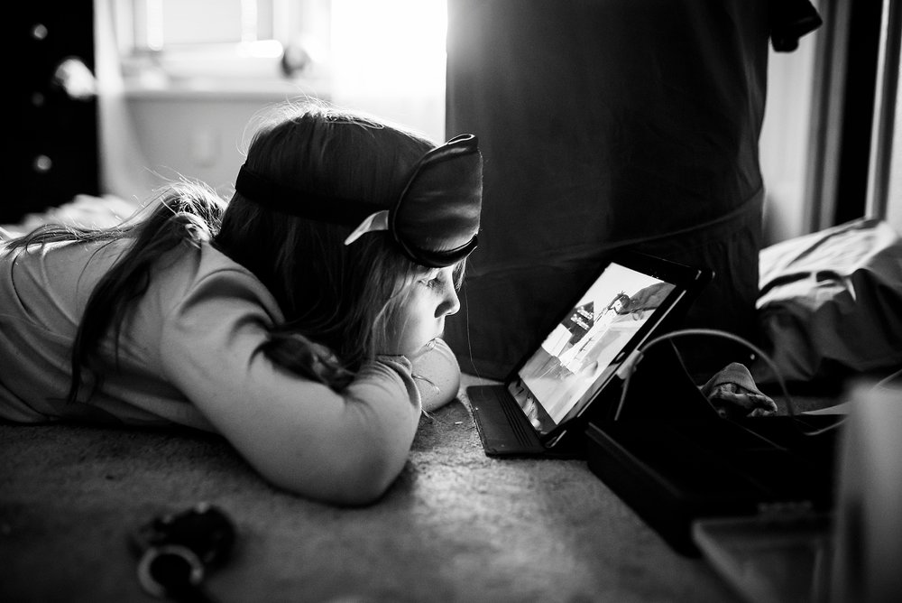 Black and white image of a little girl watching a show on the ipad on Yes Day! | Denver Candid Family Photographer