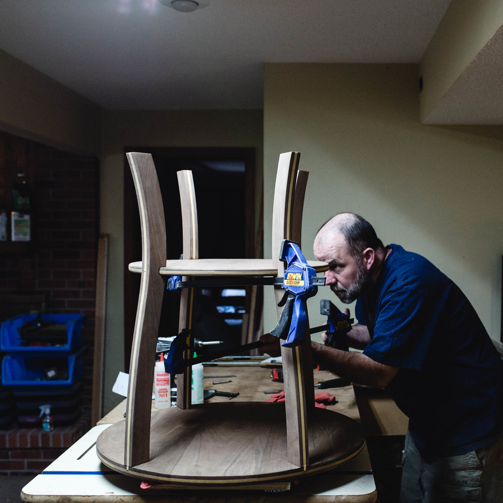 A Denver woodworker clamping a round table in his workshop. | Denver Candid Family Photographer