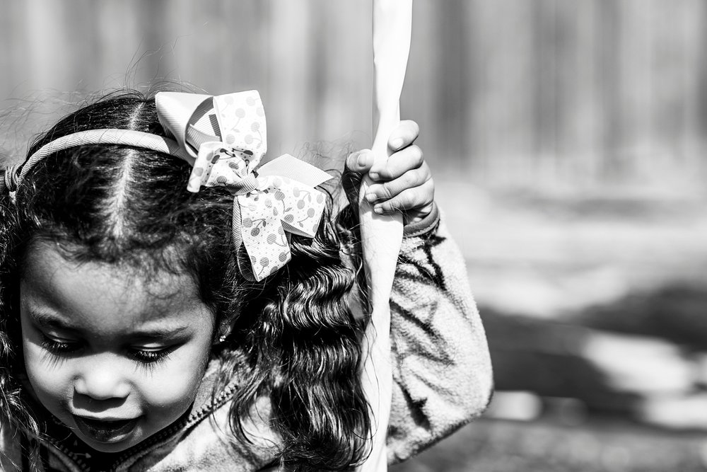 Black and white photo of a little girl swinging outside with bow in hair. | Denver Family Photographer