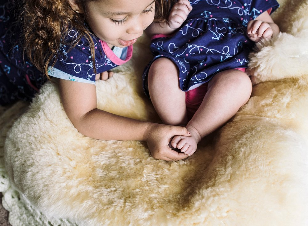 Big sister checking out newborn sister's feet during a family photography session in Denver, CO. | Family Photographer