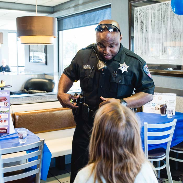 Coffee With a Cop in Greenwood Village, CO.  An officer explains his tool belt from his uniform to a child.  Denver Candid Family Photographer.