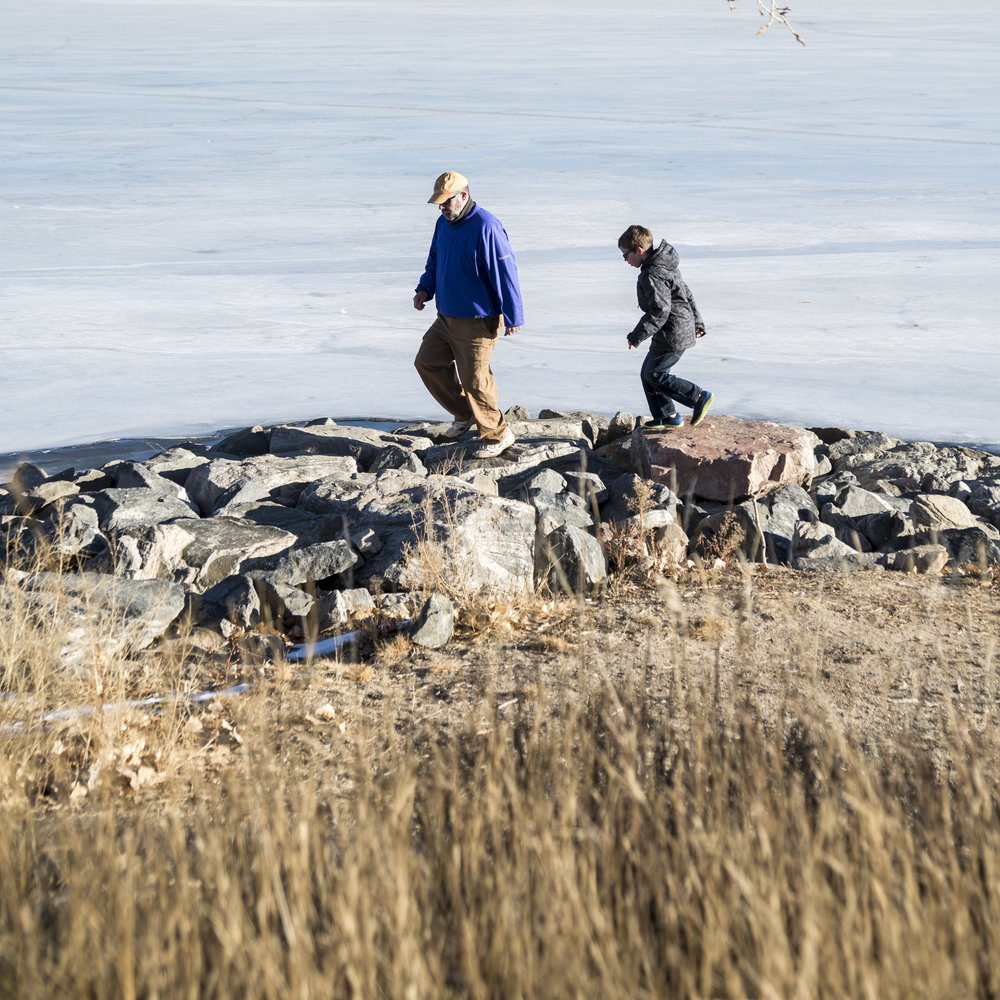 Father and son walk along the rocks in Denver's Cherry Creek Reservoir | Denver Family Photographer | Top 10 things to do in Denver with kids.