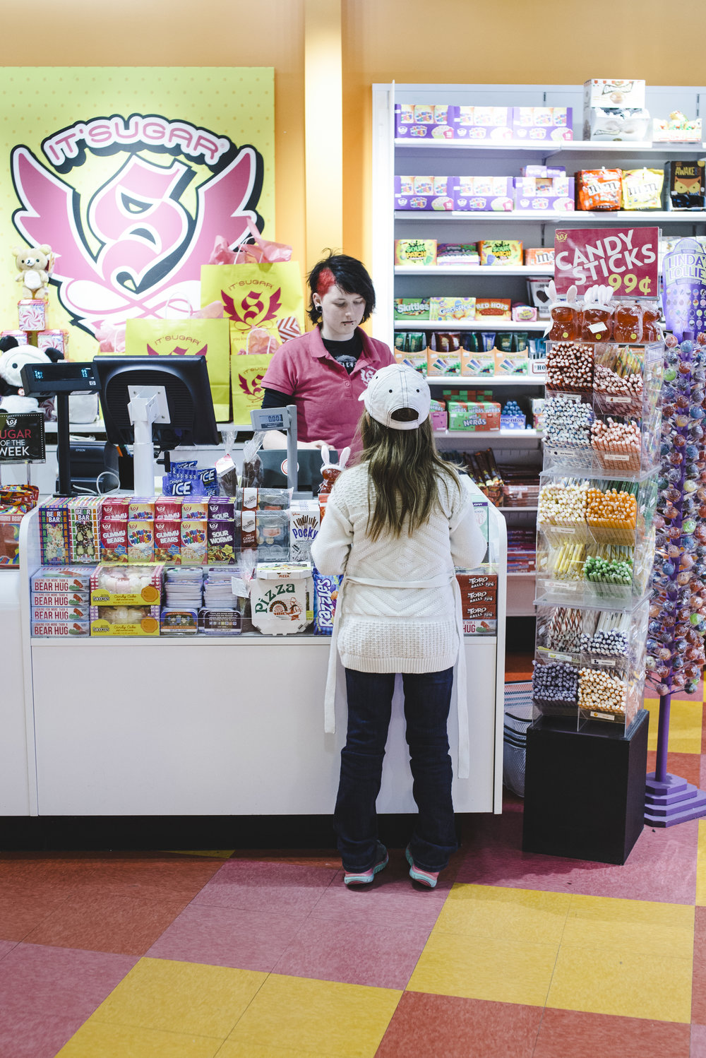 A girl buys candy at Denver's It's Sugar store on the 16th Street Mall in Colorado. Denver Family Photographer--Top 10 things to do in Denver
