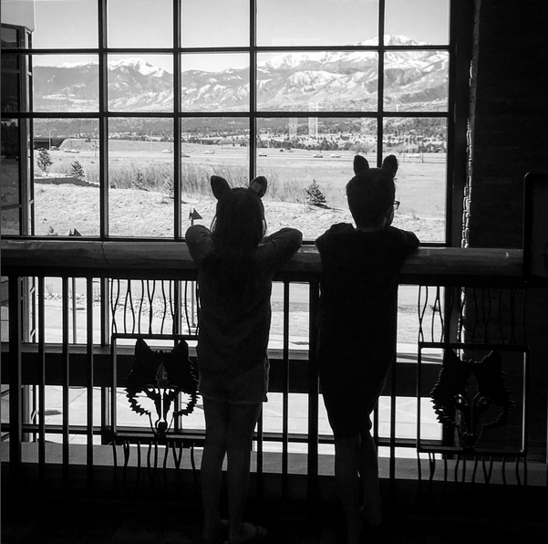 A boy and girl look at the mountains in their wolf ears at Colorado Spring's new Great Wolf Lodge. Denver Family Photographer | Lifestyle photography