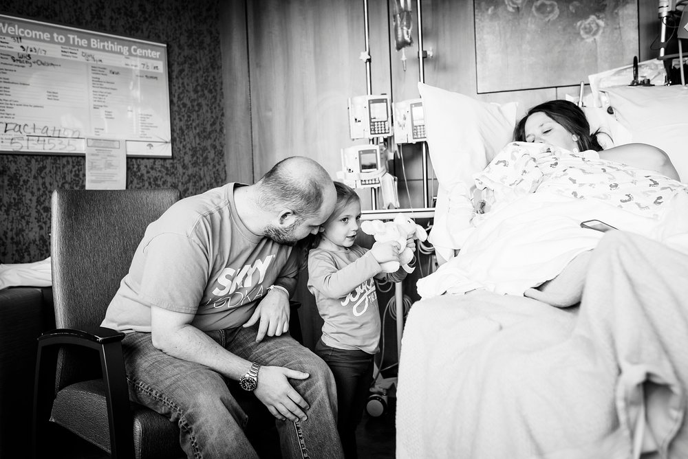 A family sits just a few hours after mom delivered a baby boy in a hospital in Denver, CO.  Denver family photography | Fresh 48
