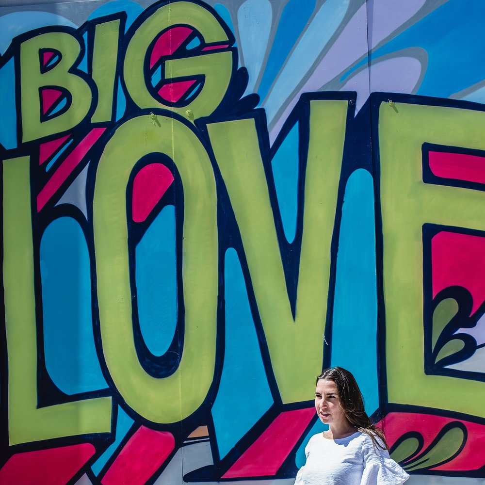 "Molly Garg poses in front of a ""Big Love"" wall mural in RiNo, Denver, Co."