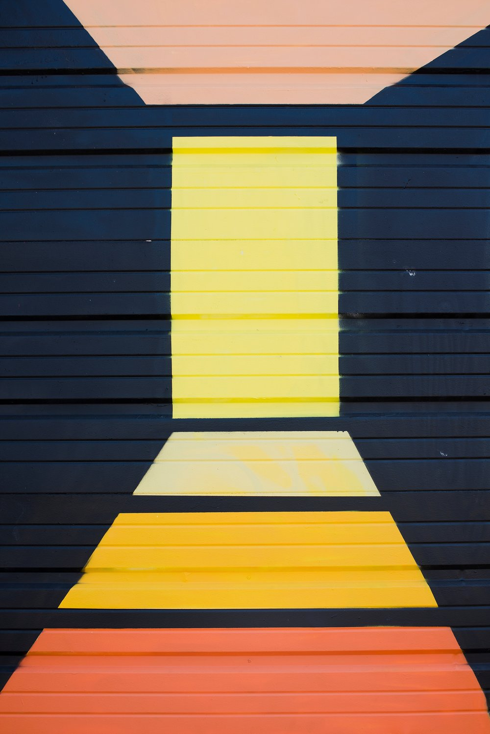 A black, yellow, and orange street art mural in RiNo, Denver, CO gives the illusion of walking toward a yellow door on the NAPCP photo challenge walk.