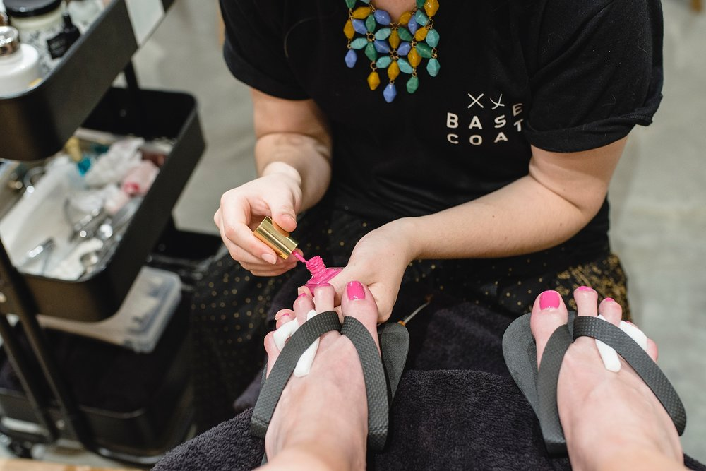 A women gets pink nail polish on her toes during a pedicure. | Base Coat Nail Salon Stapleton review by Kristiina Craven Photography