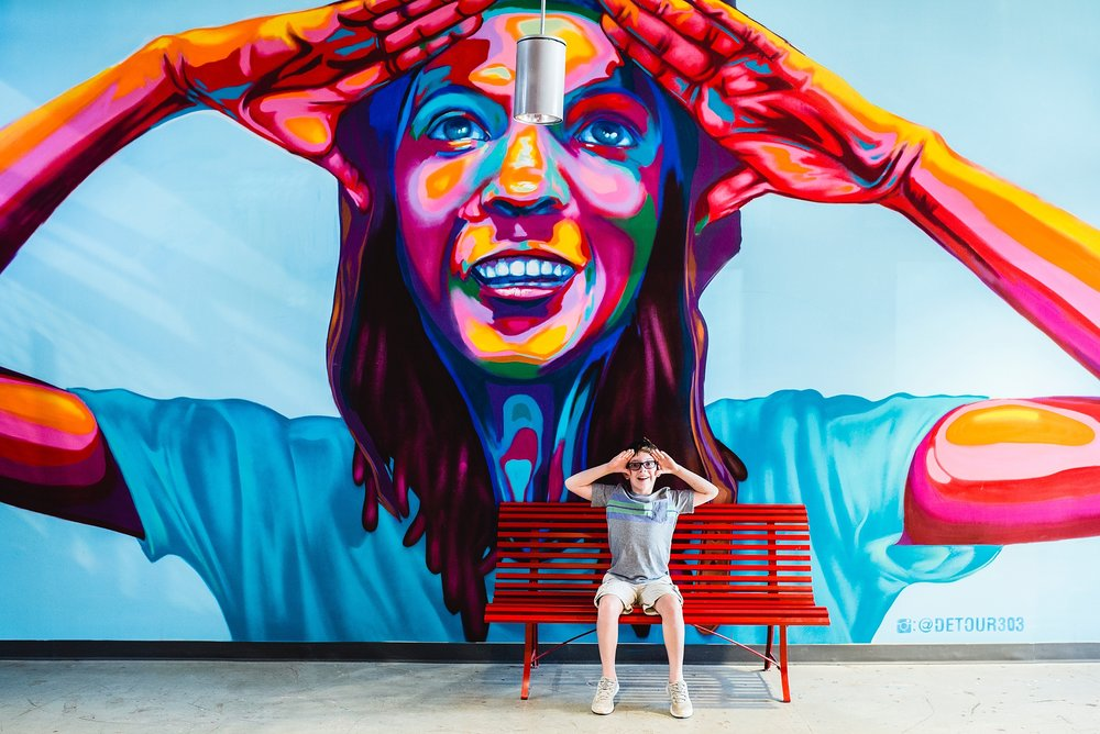 A boy mimics a huge and colorful mural in the Stanley Marketplace in Stapleton, CO. The photo is by kristiina craven photography.