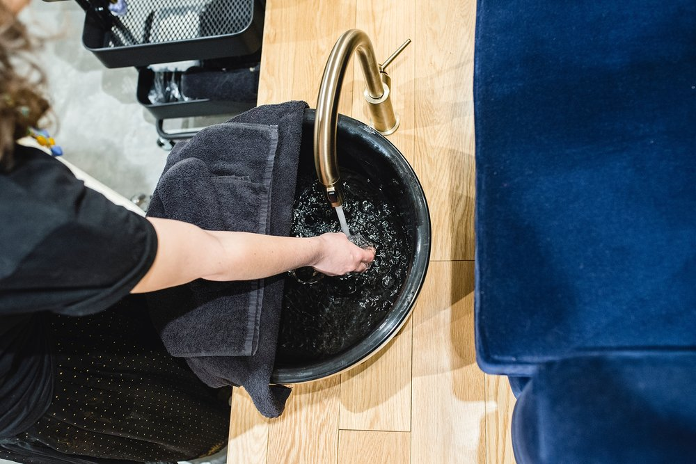 Are nail salons safe during pregnancy?  A nail tech checks the water temperature before a pedicure at Base Coat Nail Salon in Stapleton by Kristiina Craven Photography.