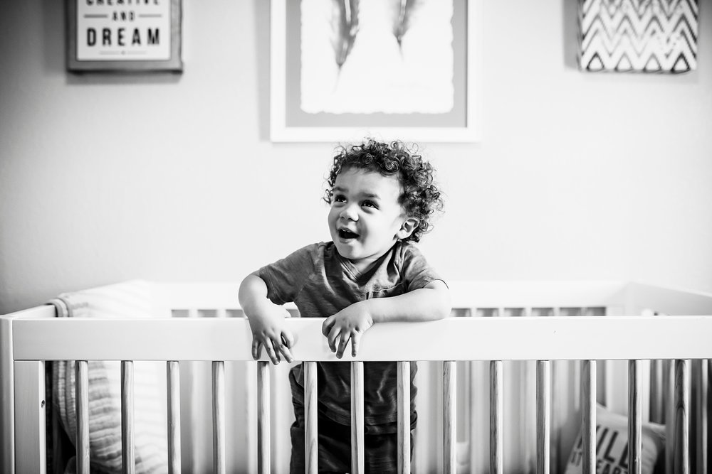 A nearly two-year-old boy jumps with excitement in his crib during his sister's newborn photo session in Denver, Co.