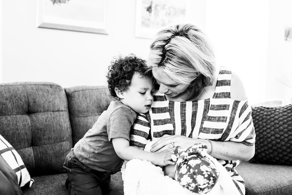 A mom gently shows her 2-year-old son how to comfort his newborn baby sister at their in-home photo session in Denver, CO.
