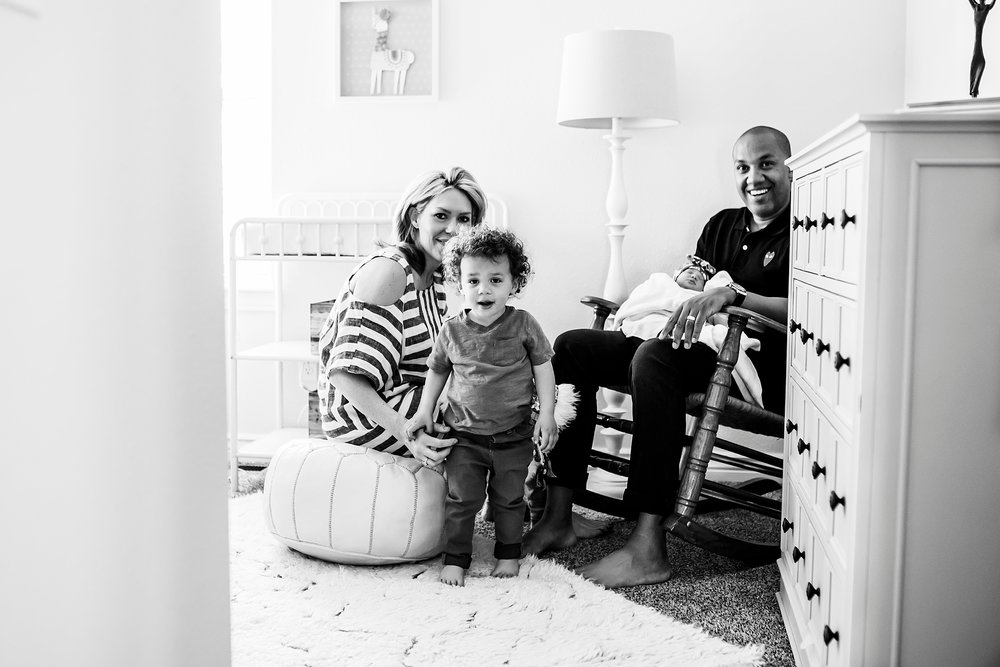 Now a family of four, everyone gathers in the newborn baby girl's nursery at her in-home photo session in Denver, CO.