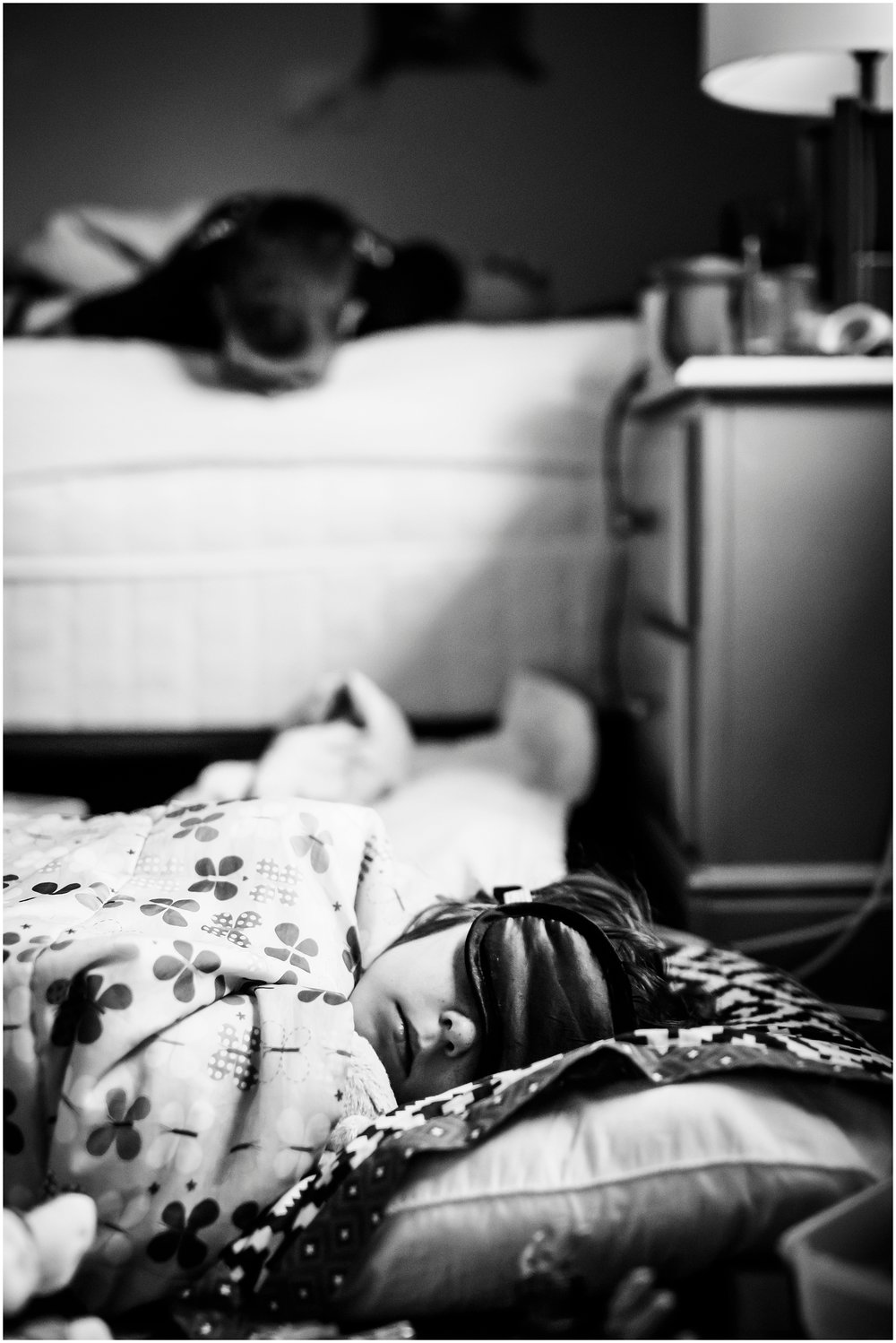 A sister sleeps with her sleeping mask on while her brother waits for her to wake up from their sleepover in Denver, CO. | Kristiina Craven Family Photography