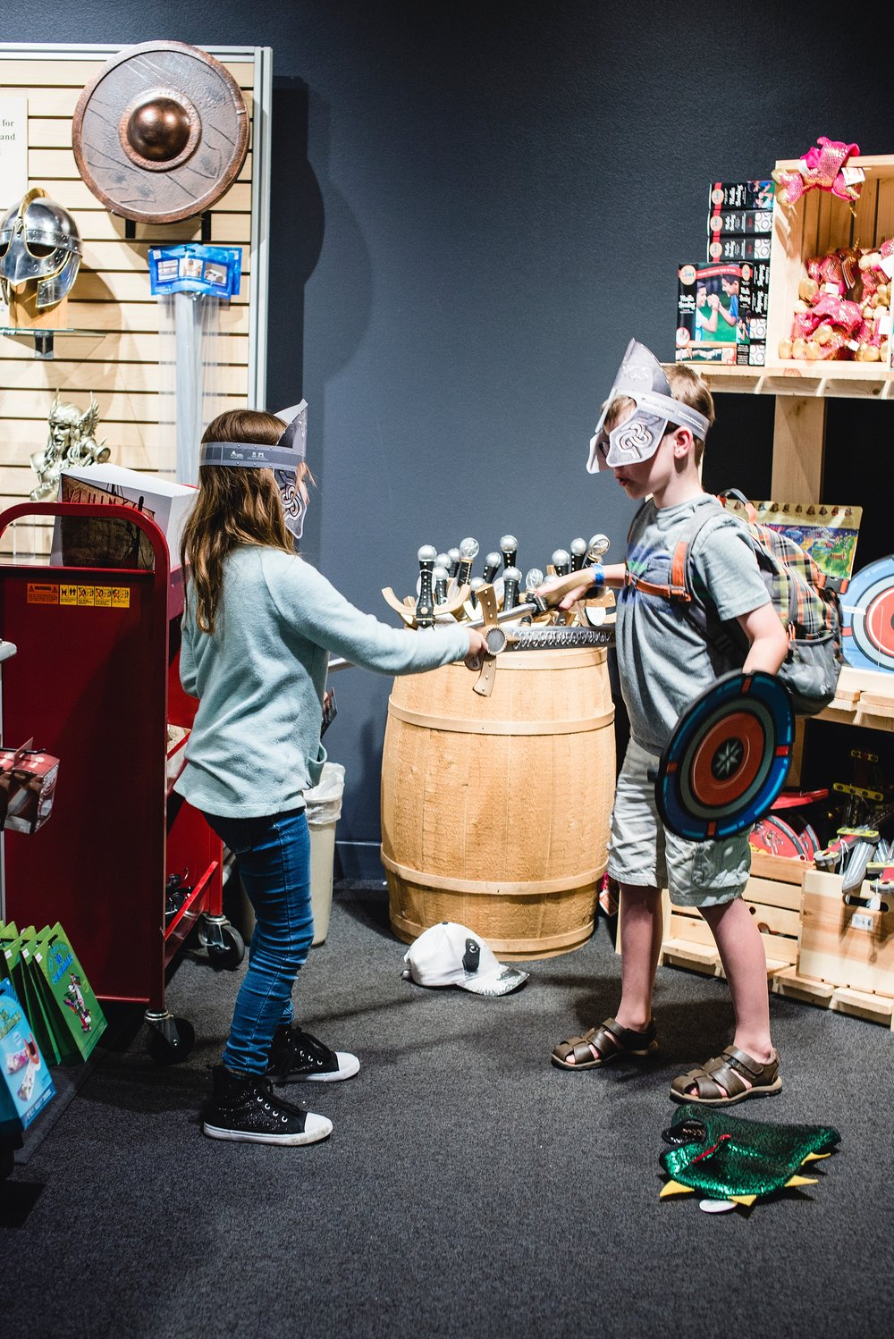 Two pre-teen kids play with the viking swords in the gift shop of the Denver Museum of Nature and Science in Colorado. Photo by Kristiina Craven Photography