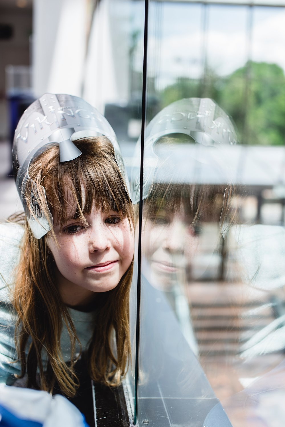 A girl sits against a glass wall and her reflection shows at the Denver Museum of Nature and Science. Photo by Kristiina Craven Photography