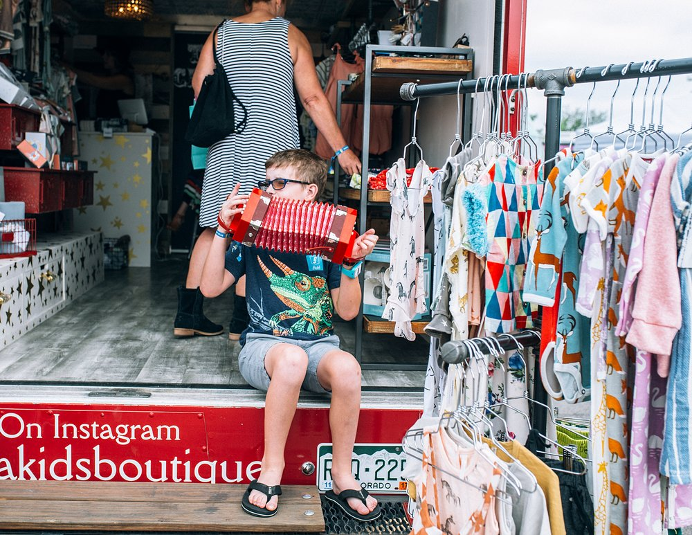A boy plays a toy accordion on the steps of The Circus, a Kids' Mobile Boutique, at the summer Denver Flea 2017.  Photo by Kristiina Craven Photography.