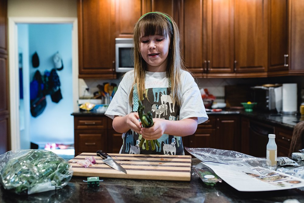 a girl cooks a blue apron meal in her new apron from Penni Olive.  photo by kristiina craven photography.