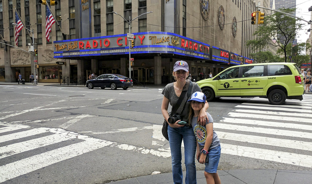 The best camera is the one you have on you.  A mother and daughter stand on a corner in New York City near Radio City Music Hall.  Photo by the husband of Denver Family Photographer, Kristiina Craven.