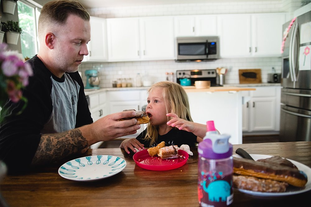 A dad feeds his daughter some La Mar's donuts in Highlands Ranch, CO, during a maternity photo shoot with Kristiina Craven Photography.