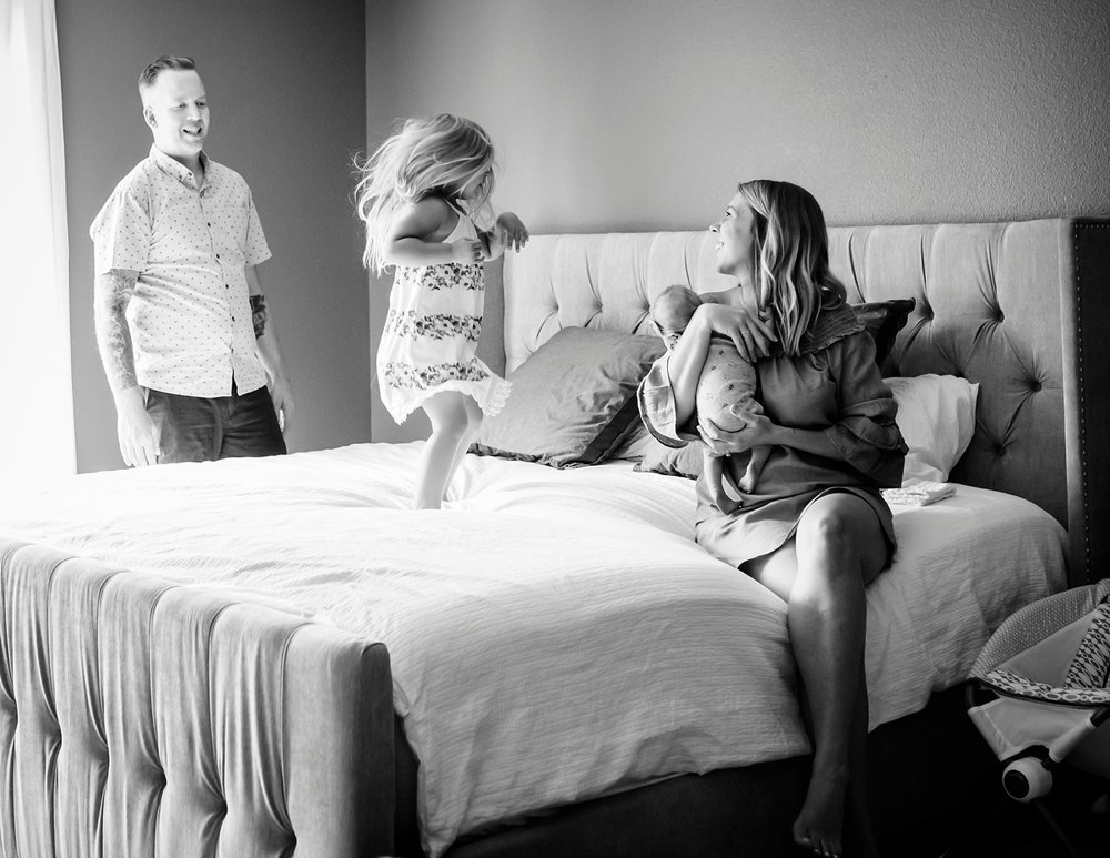 A toddler twirls on her parent's bed as they look on during a lifestyle newborn photo shoot in Highlands Ranch, Colorado.  With Kristiina Craven Photography.