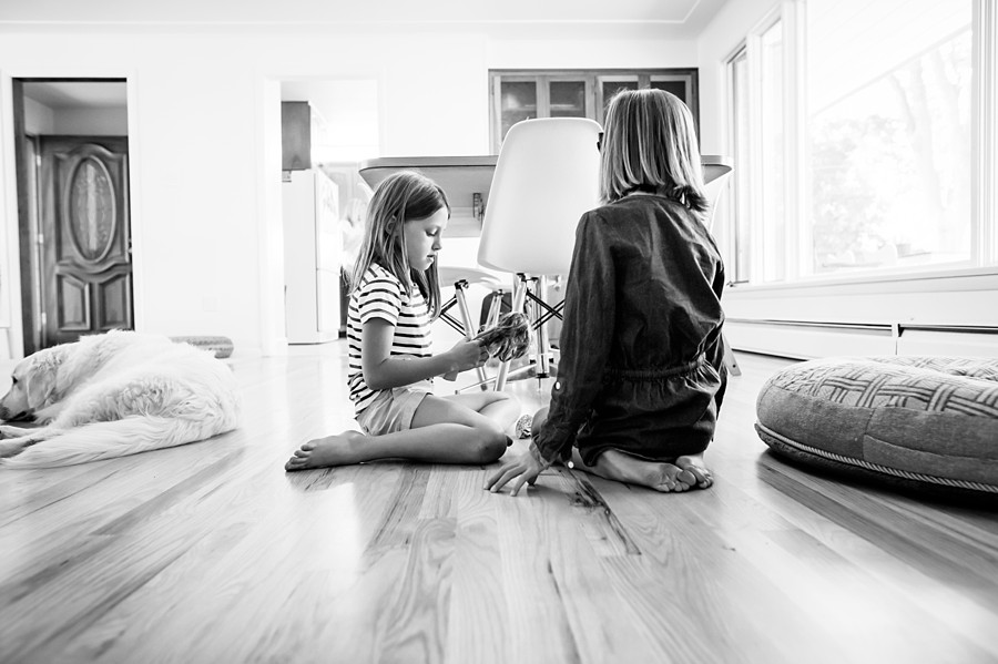 Two young girls play Barbie while their dog rests nearby in this black and white image by Kristiina Craven Photography in Denver, Colorado.