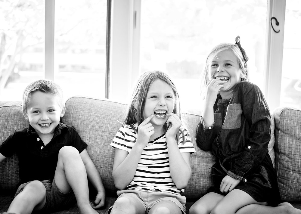 A black and white photo of young kids laughing and being silly during a family photo shoot near Denver, Colorado.