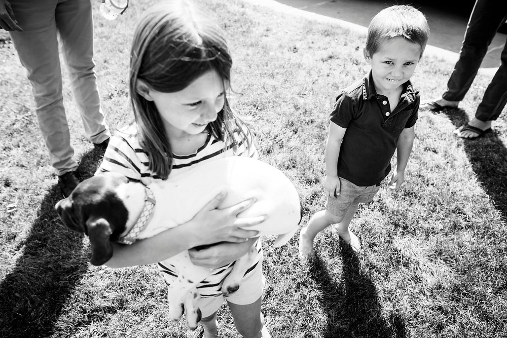 Siblings hold on to their cousin's new puppy during a lifestyle photo shoot in Louisville, CO.