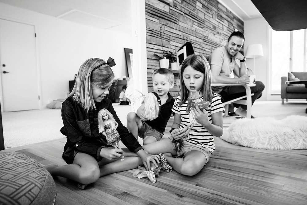 A little brother joins the girls to play Barbie near Denver, Colorado.
