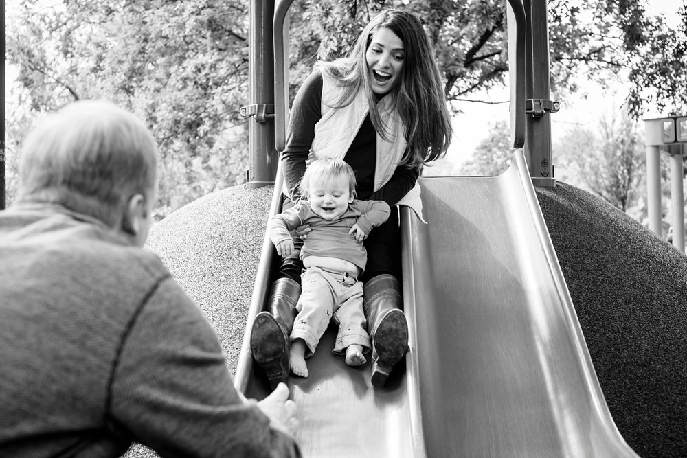 A mom rides the slide with her toddler son in Denver, Colorado.  Black and white family lifestyle photography with Kristiina Craven Photography.
